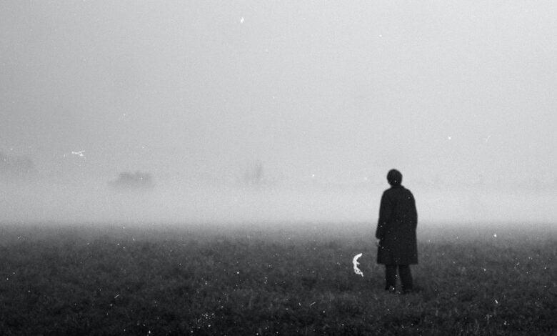A shadowy figure stands in an open field