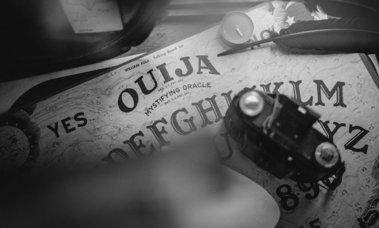 a ouija board with a quill, a candle, and a camera sitting on top of it