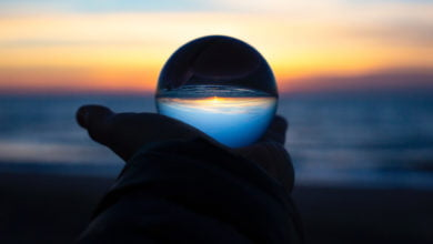 A hand holding a clear sphere, which reflects the sunset over the ocean