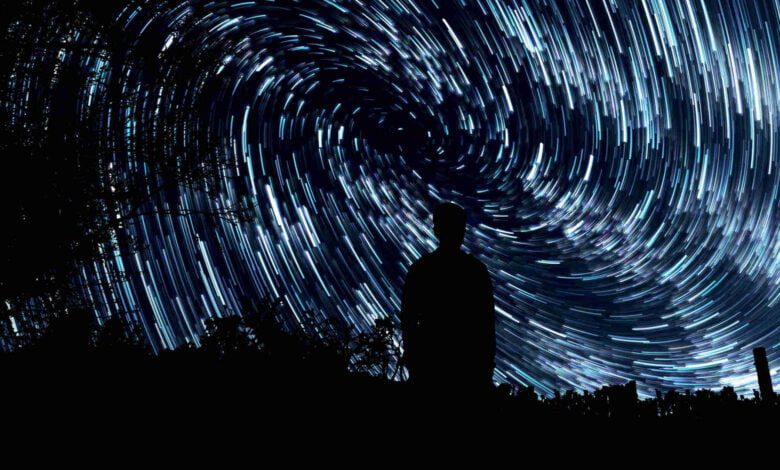 A man stands in front of a spiral of stars