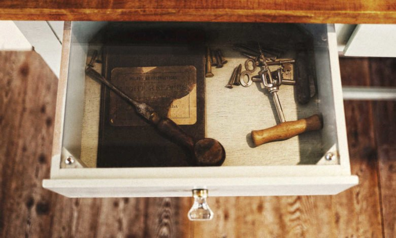 A desk drawer with several old items inside