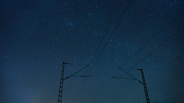 Power lines under a star-filled night sky