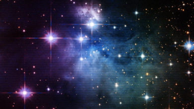 A multi-colored galaxy, with purple and blue gas clouds and bright white stars