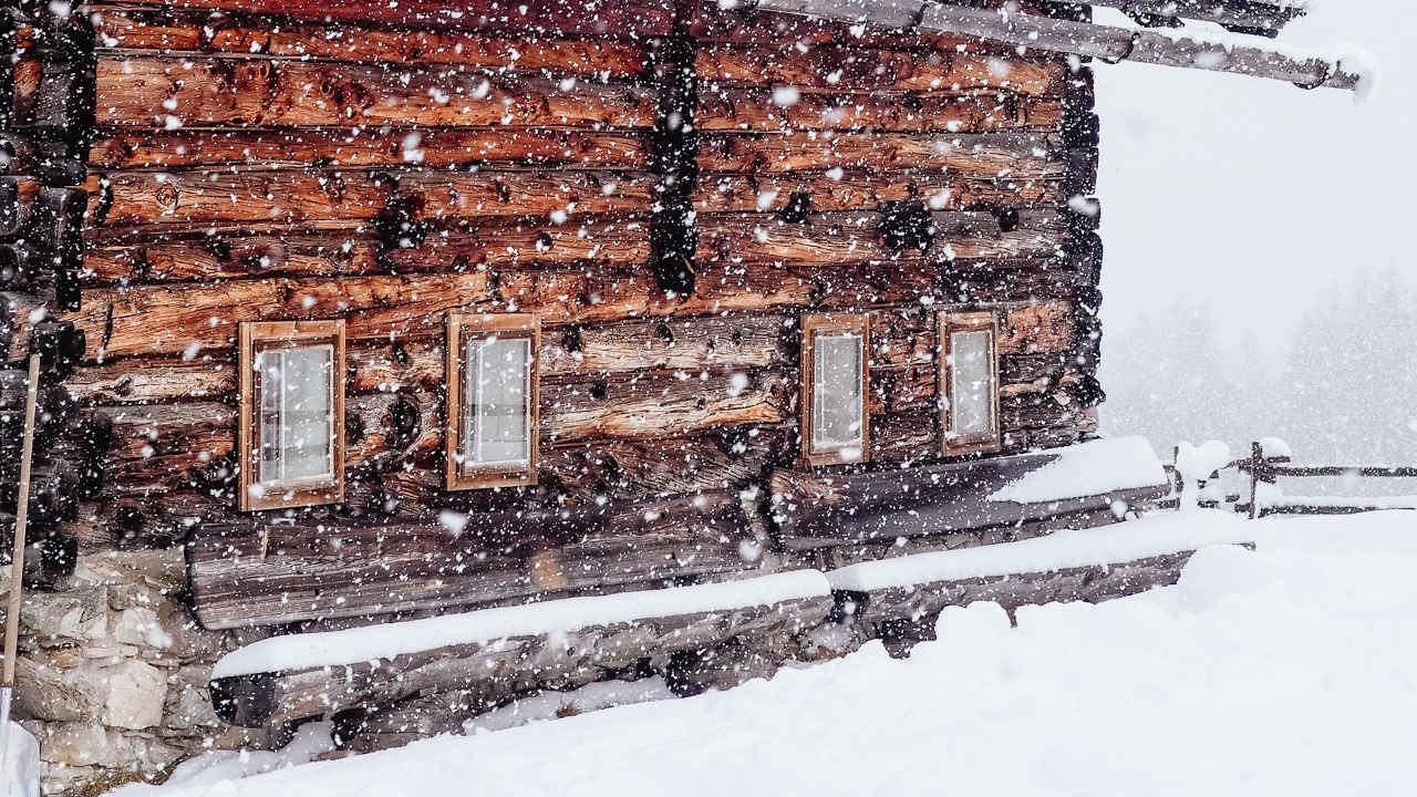 a wood cabin in a snow storm