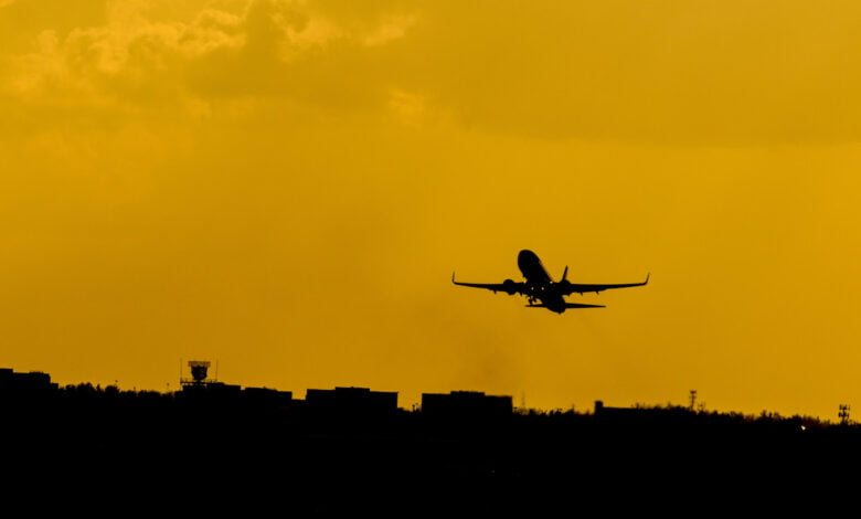A plane takes off against a yellow sky