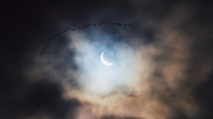 A solar eclipse hides behind clouds