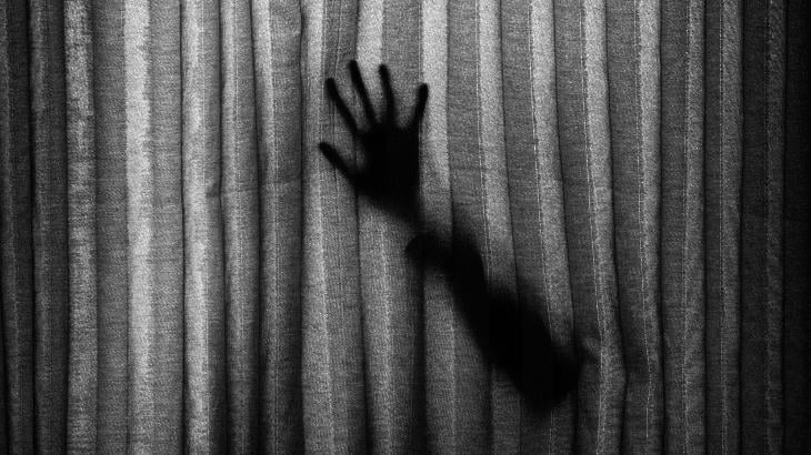 A shadowy hand presses against a curtain