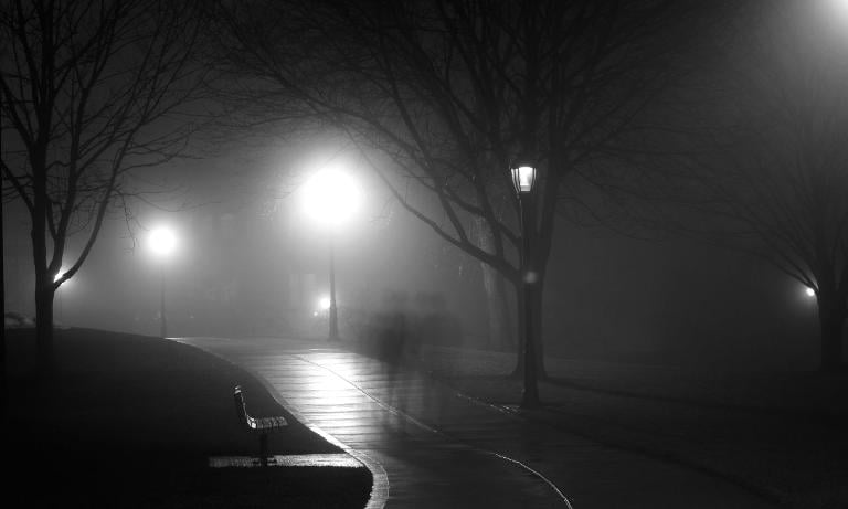 A shadowy figure approaches from a poorly lit road