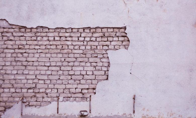A broken wall revealing bricks underneath