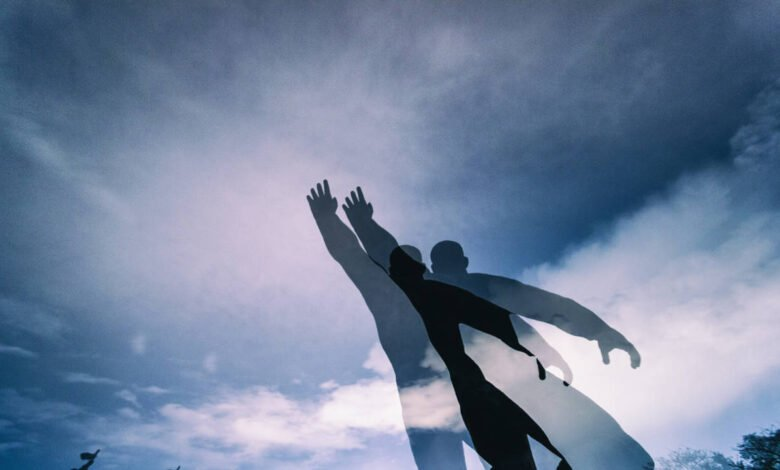 Statue of a man reaching out to the sky in double exposure