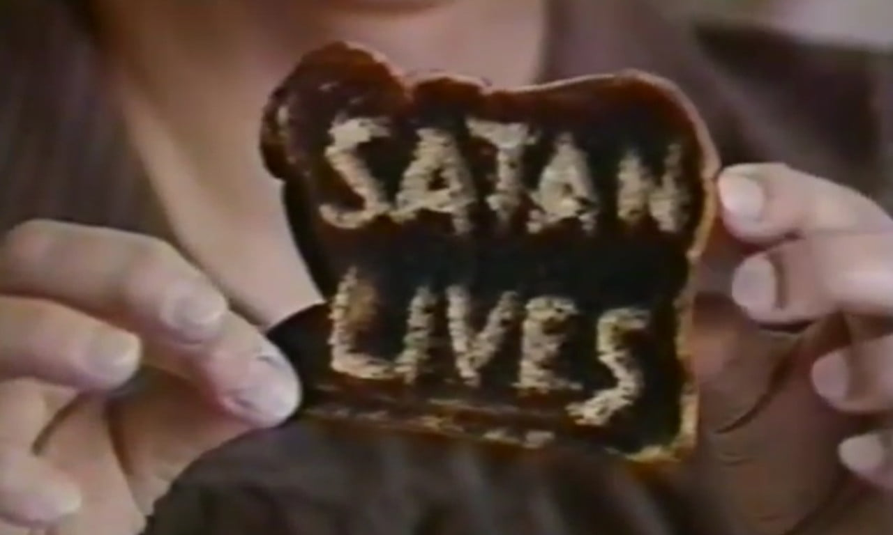 """June O'Brien holds up a piece of toast that says """"Satan Lives."""""""